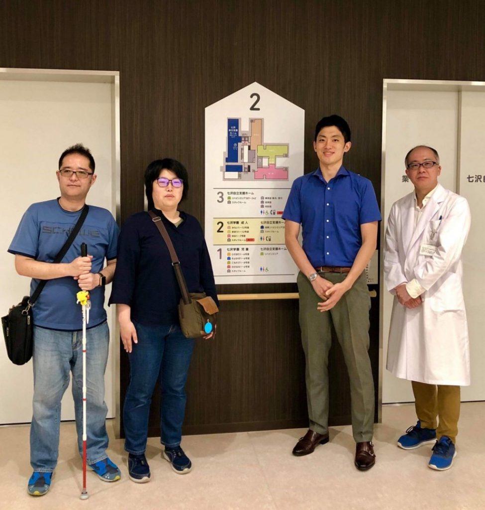 エレベーターの前で、久米川先生とSpotliteの渡辺、下田、高橋が記念撮影している画像。
