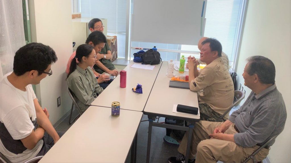 会議室で話をするボランティアさんとスタッフの画像。