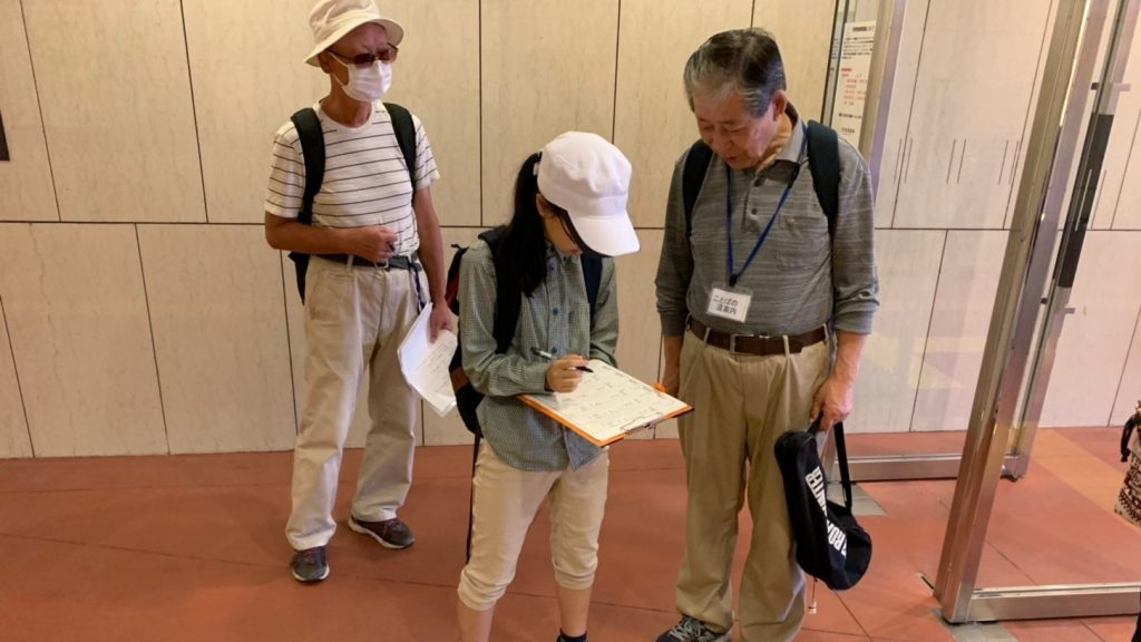 駅構内で、ボランティアが必要な情報をメモしている画像
