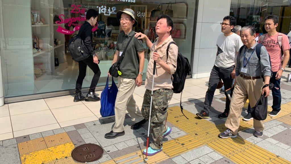 市川さんを誘導しながら歩くボランティアさんの画像
