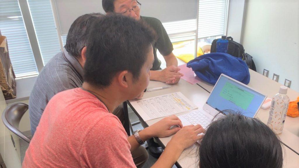記録用紙を見ながらパソコンに入力するボランティアさんの画像