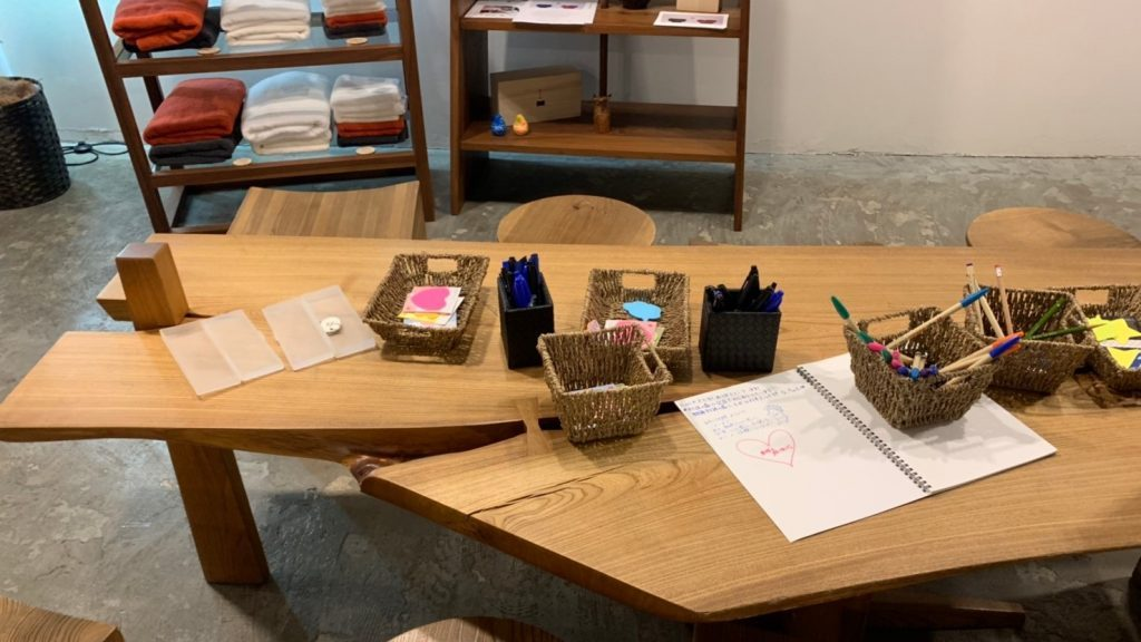 木製の机の上に、ポストイットやペンが置かれている画像。