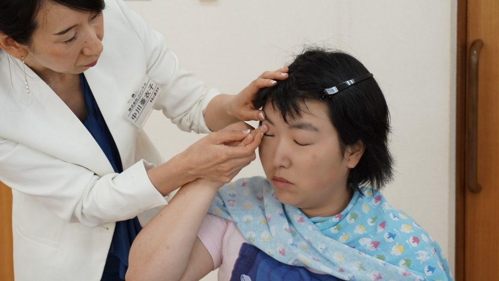 中川さんが参加者の薬指を持って、眉毛の上にチークを塗る画像。