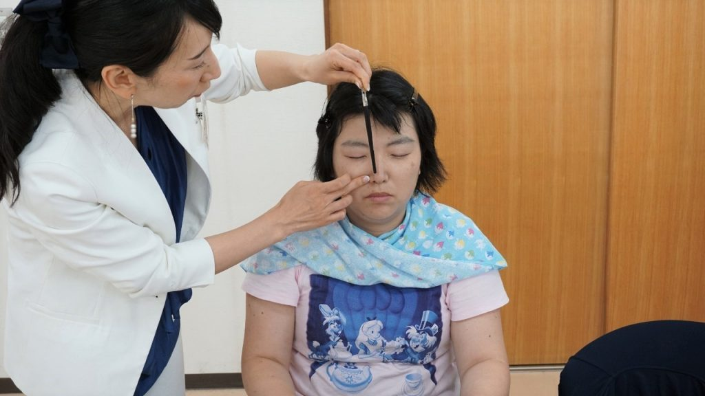 中川さんがブラシの柄を使って参加者の眉毛のバランスを確認している画像。