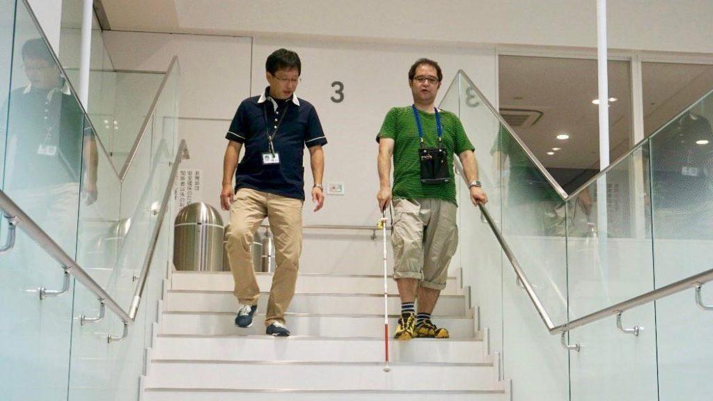 左手で手すりに捕まりながら階段をおりる渡辺と、横で見守る佐藤訓練士の画像