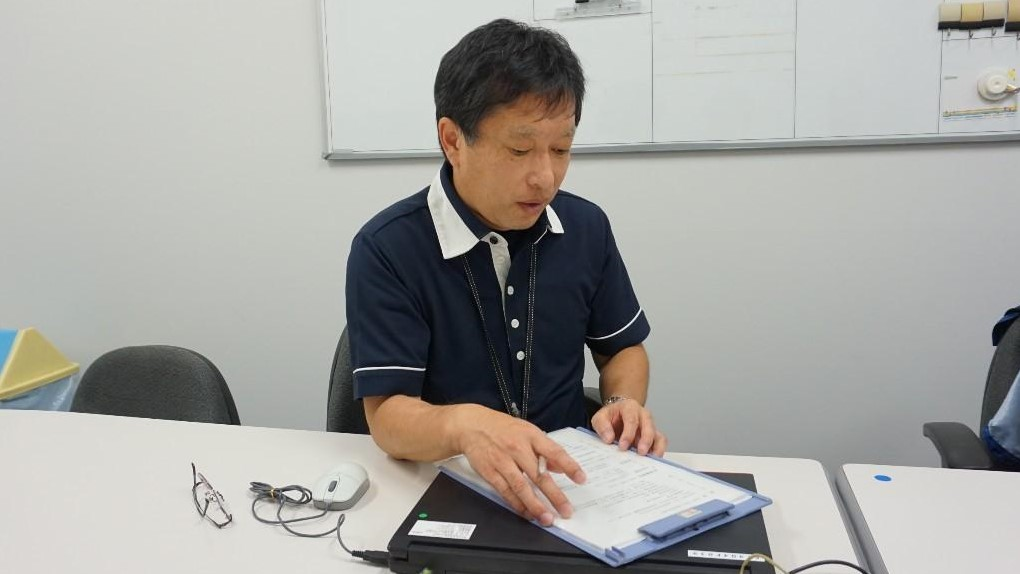 佐藤訓練士が書類を見ながら説明している画像