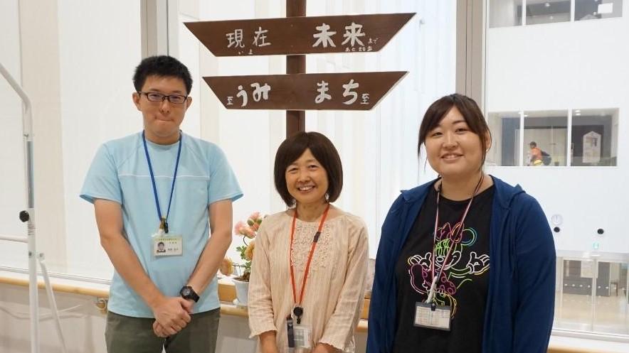 エレベータ前で訓練士三人が笑顔で並んでいる画像