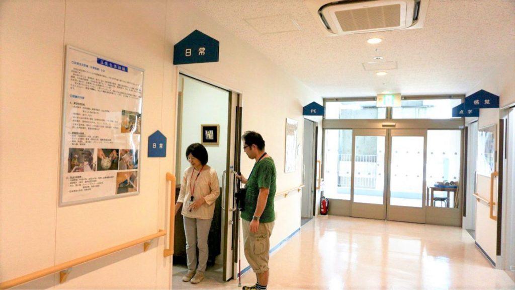 日常訓練室の入り口で、角石訓練士と渡辺が写っている画像。