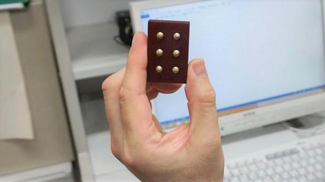 手のひらサイズの点字一文字分のブロックを手に持った画像