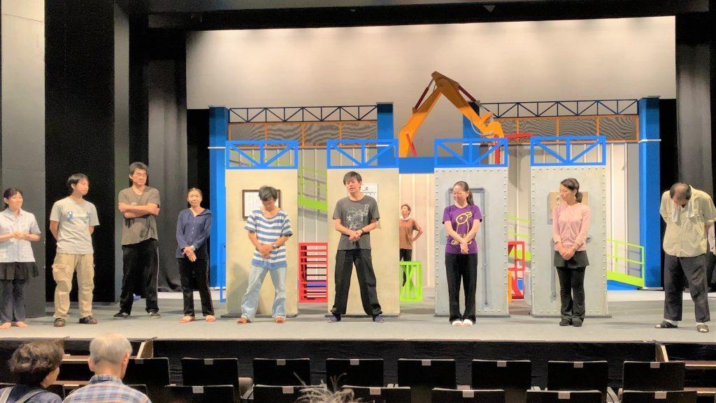 舞台の上で俳優が一人ずつ自己紹介している画像。