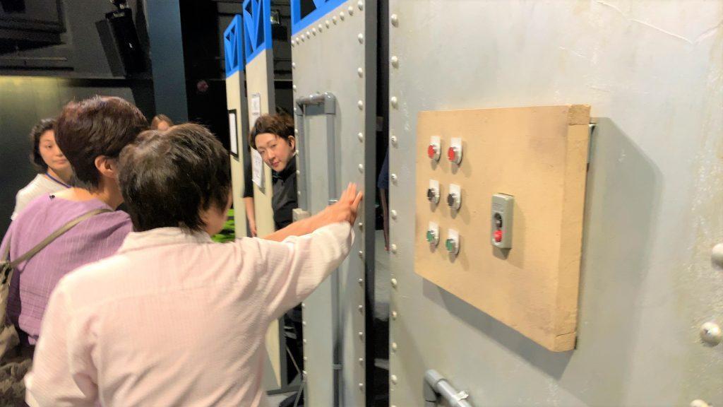 舞台のセットを触って確認する視覚障害者と様子を説明する劇団員の画像。