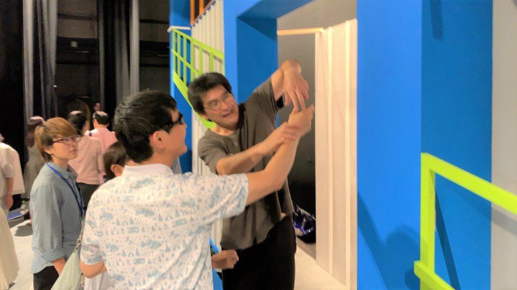 劇団員が腕を使って視覚障害者にショベルの形を伝えている画像。