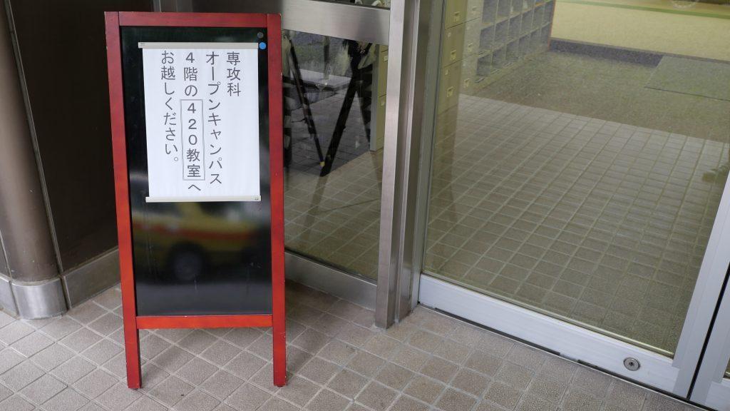 学校の入口に、オープンキャンパスの案内板が置かれている画像。