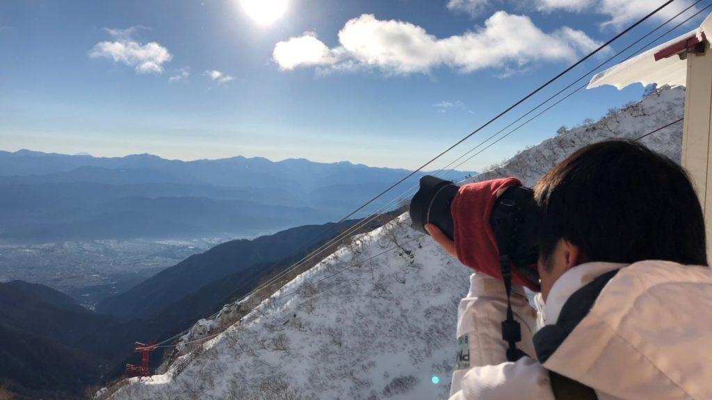 安藤さんが山頂から日の出の様子を望遠カメラで撮影している画像。