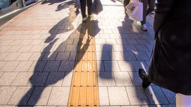 点字ブロッグが敷設されている道を歩く人影が写っている画像。