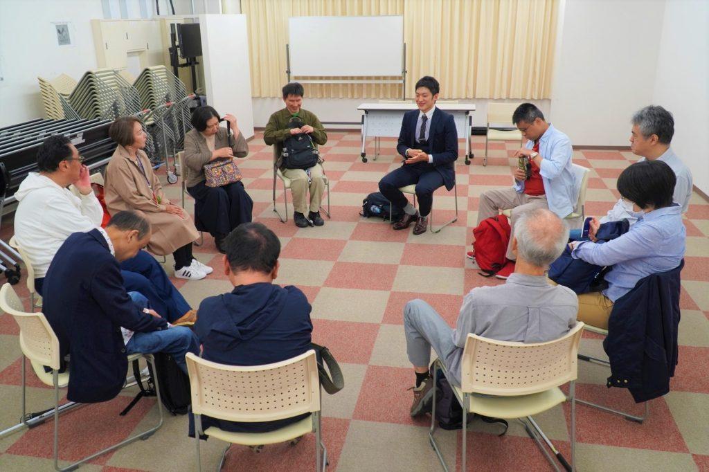 イベントの参加者が円形になって椅子に座り、話をしている画像。