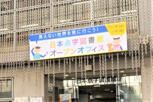 日本点字図書館の入り口の画像。カラフルなオープンオフィスの看板が掲げられている画像。