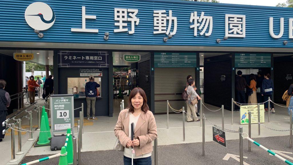 上野動物園の入り口をバックに丸山さんが立っている画像。
