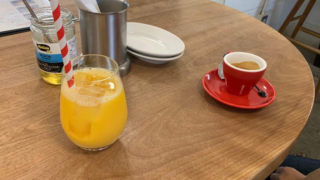 カフェのテーブルの上にオレンジジュースとエスプレッソが置かれている画像。