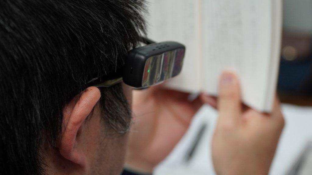 エンジェルアイスマートリーダーを使って本を読む様子を後ろから撮影した画像。