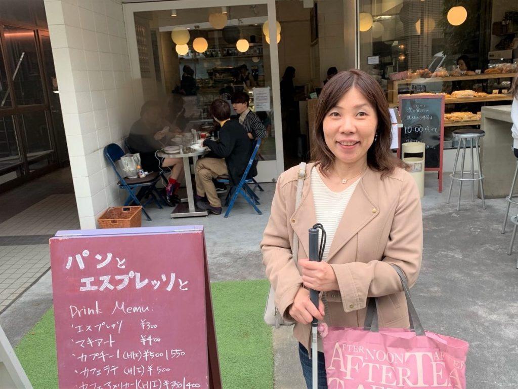 カフェの看板の横で丸山さんが笑顔で立っている画像。
