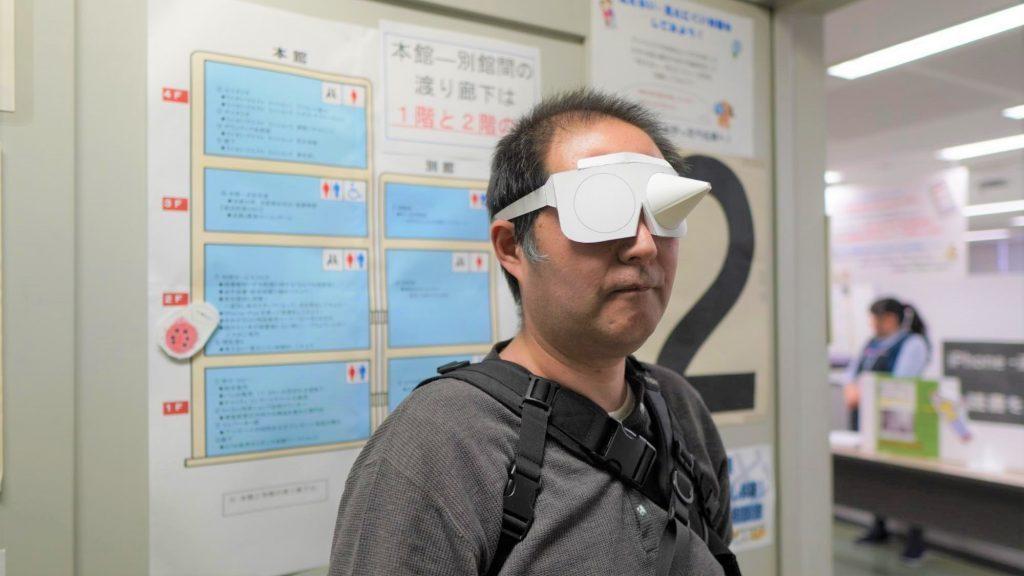 スタッフの渡辺が視野狭窄の体験眼鏡をかけている画像。