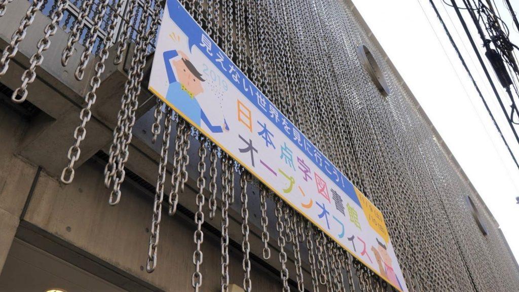 日本点字図書館入り口の看板を下から見上げるように撮影した画像。