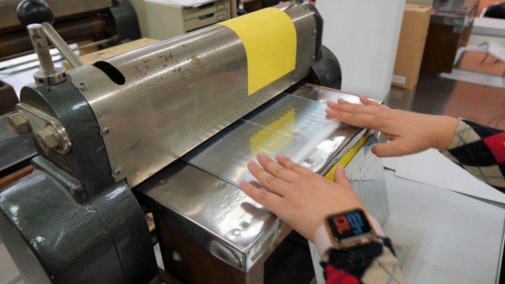 亜鉛板印刷を行う機械に亜鉛板を通している画像。