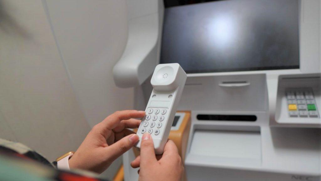 ATMを操作する受話器をアップで撮影した画像。