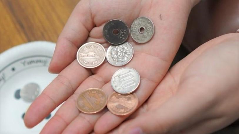 50円玉と5円玉を間違えて選んだ小銭を手のひらに乗せている画像。