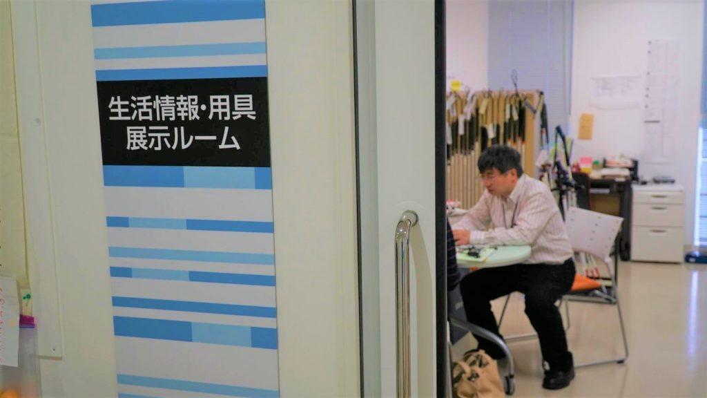 部屋の中の机で、視覚障害者に説明している職員の画像。