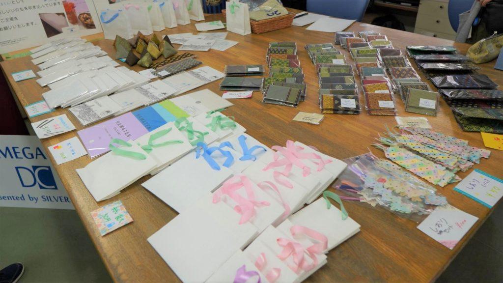 点字用紙で作成された封筒や折り紙、紙袋などが並べられている画像。