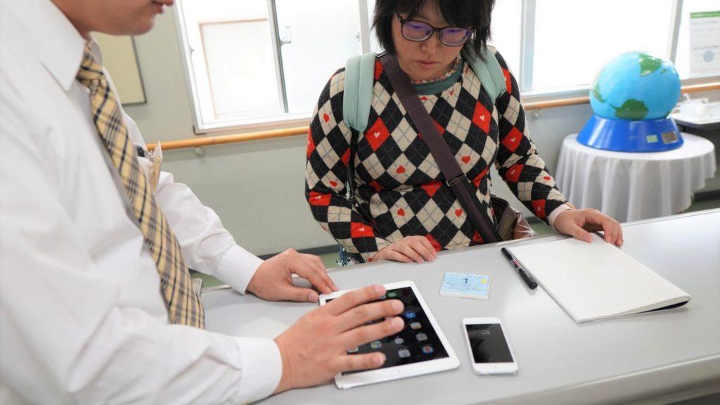 職員さんにiPadの便利な使い方を教えてもらっている画像。
