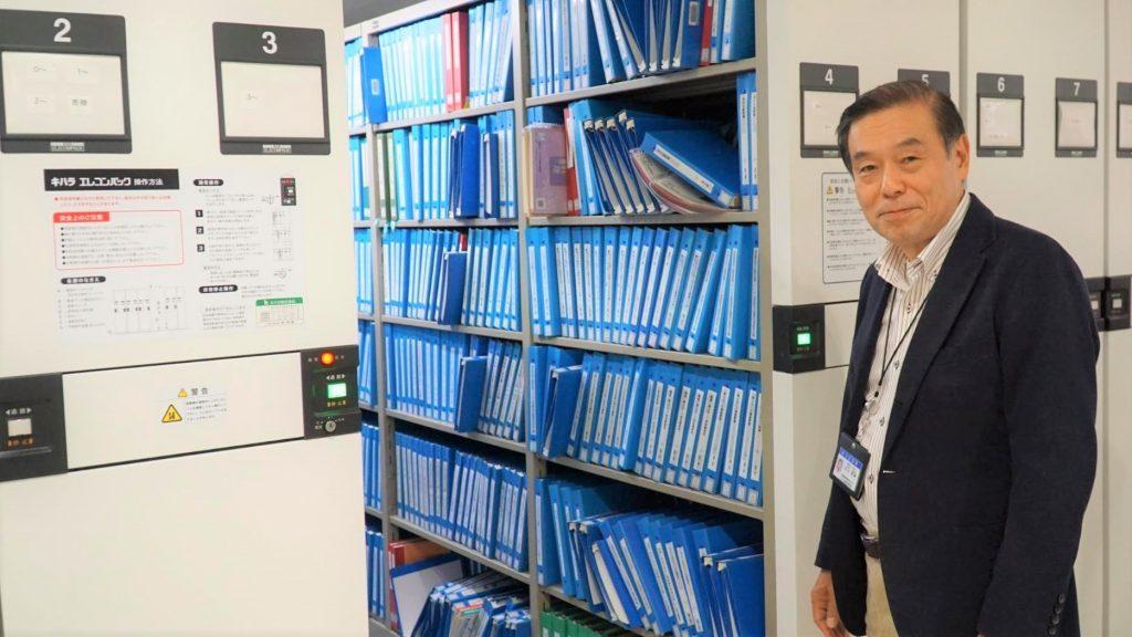 書庫の前で、センター長の杉山さんが立っている画像。