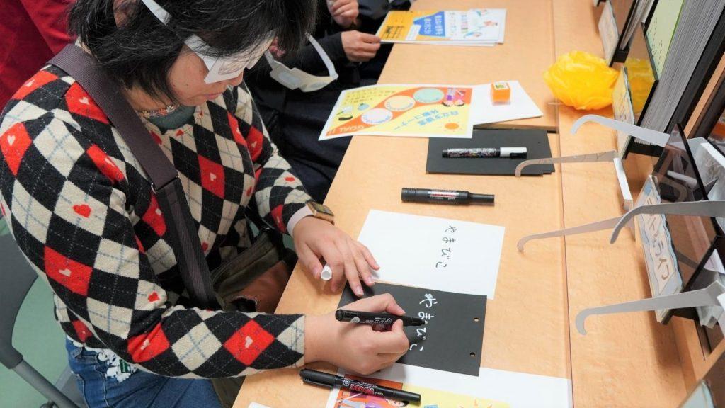 白濁状態の眼鏡をかけて、白と黒の文字を書いている画像。