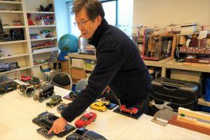 大内さんが自動車の模型を触って説明している画像。