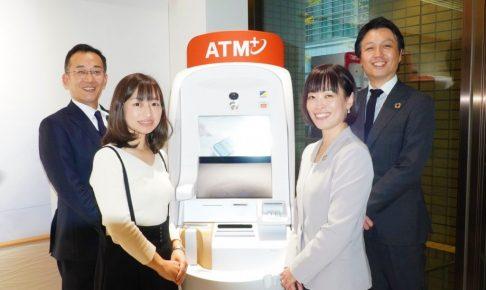 セブン銀行のATMの脇にスタッフ4名が笑顔で立っている画像。