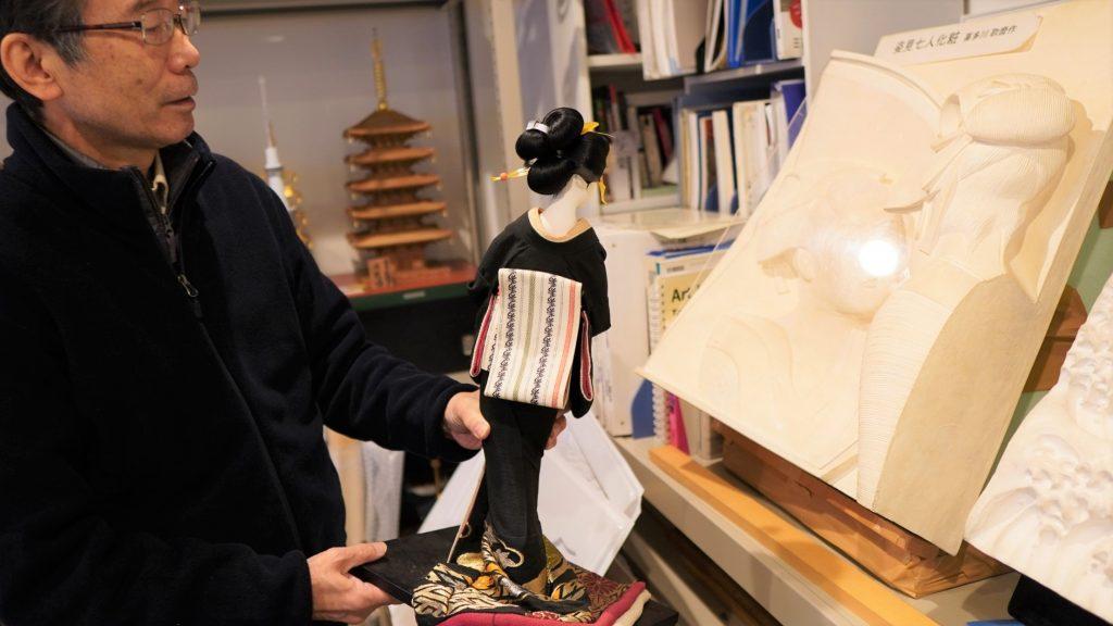 大内さんが着物をきた女性の模型を手に持っている画像。