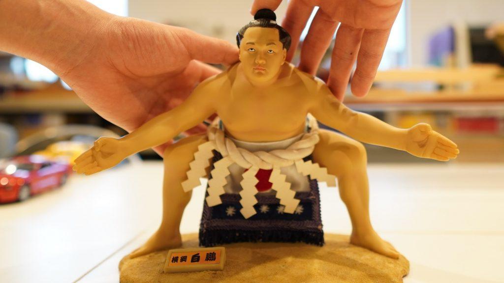 横綱白鵬が土俵入りしている模型を両手で触っている画像。