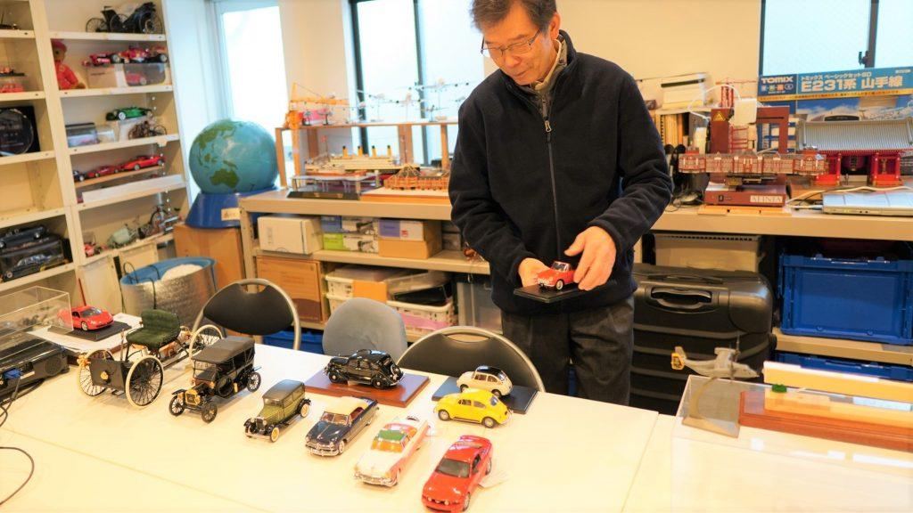 模型を並べて自動車の変遷を説明する大内さんの画像。