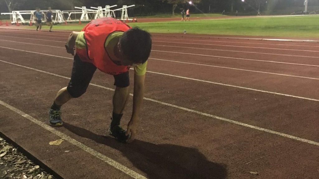 陸上競技場でスタート練習をするMさんの画像。