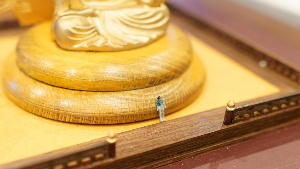 大仏の下に同じ模型の小さな人の模型を置いている画像。