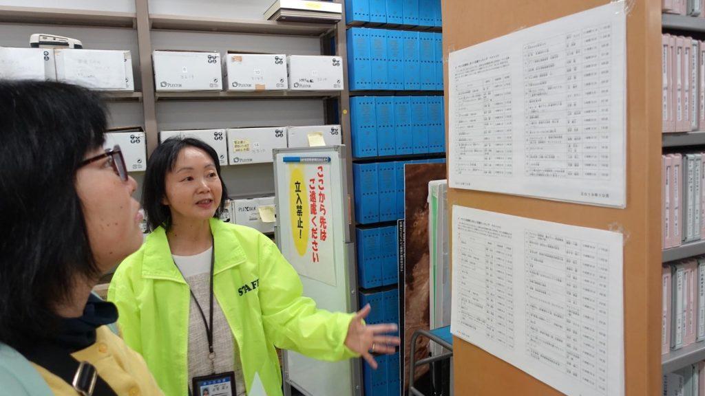 職員が、張り出された紙の内容を説明している画像。
