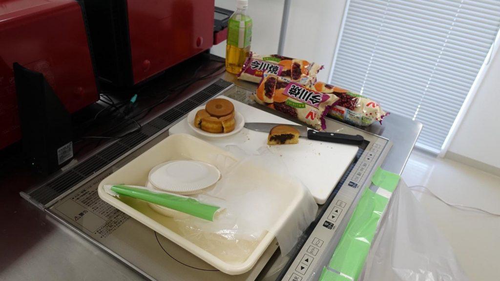 冷凍食品やタッパーが置かれている調理体験ブースの画像。