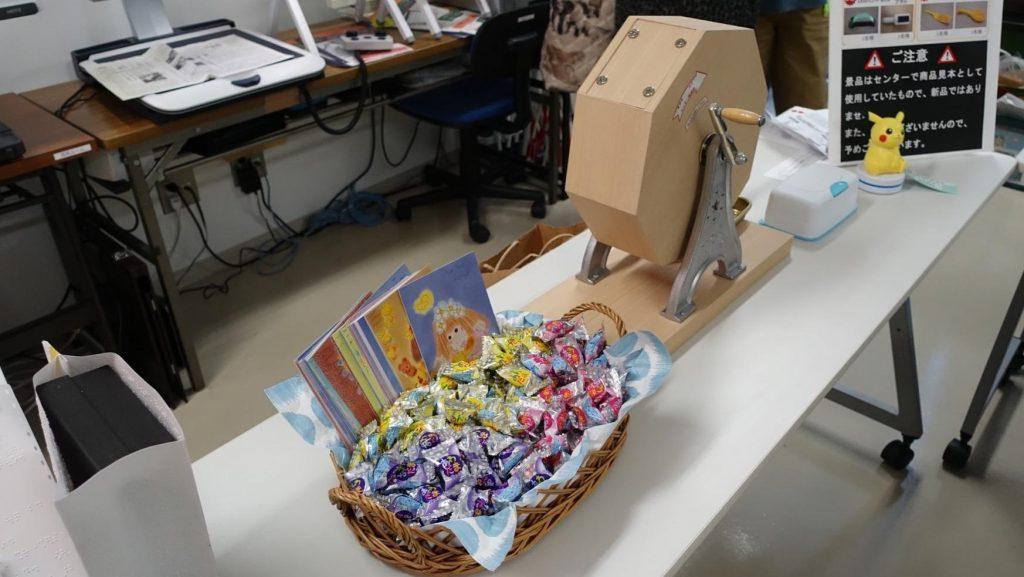 回すと玉が出る抽選機と箱に入った景品の画像。