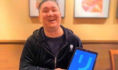 井上さんが笑顔でアイパッドを手にもっている画像。