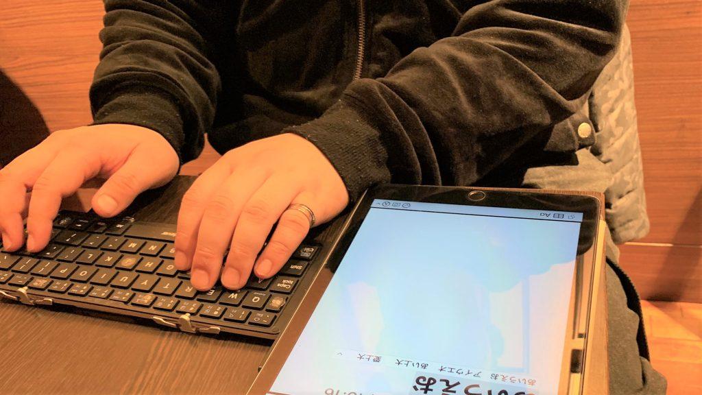 無線接続のキーボードでアイパッドに文字を入力する井上さんの手元の画像。