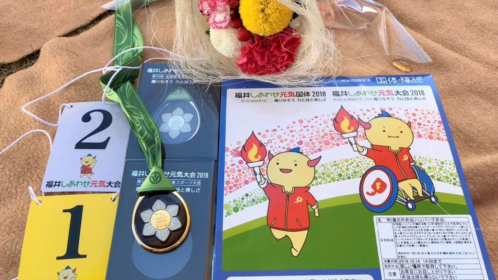 全国障害者スポーツ大会のメダルとお弁当を撮影した画像。
