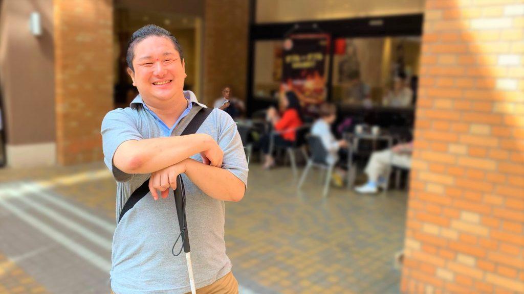 カフェの前で笑顔で立っている井上さんの画像。