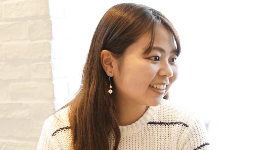 カフェの中で笑顔で話をする櫻井さんの画像。